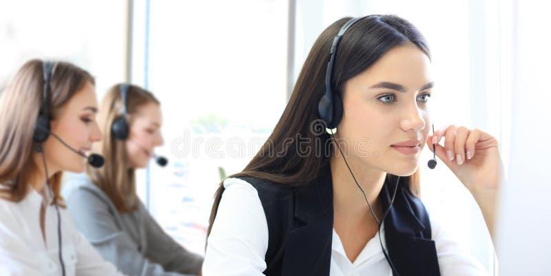 可爱的正面年轻买卖人和同事在电话中心办公室 库存照片