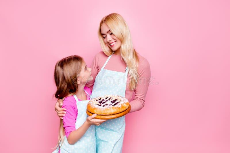 可爱的母亲和女儿演播室画象,相连鲜美饼用里面果酱,互相看,站立在pi 免版税库存图片