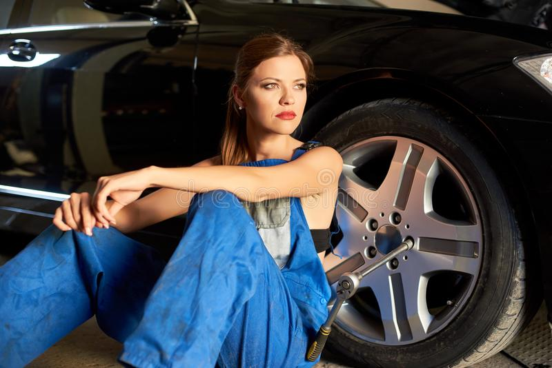 可爱的汽车机械师女孩在黑汽车附近轮子坐 库存图片