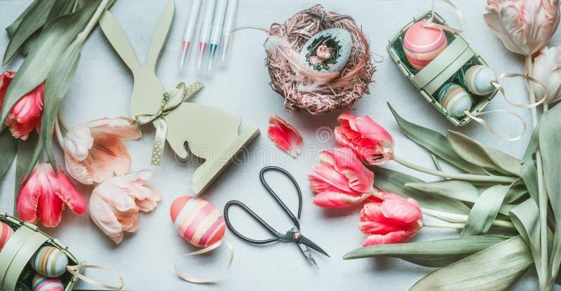 可爱的淡色复活节平的位置用鸡蛋、鸟鸡蛋、羽毛和郁金香、剪刀和标记 复活节问候准备,顶面v 图库摄影