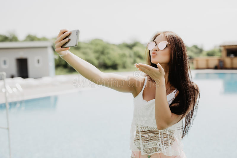 可爱的深色的女孩特写镜头selfie画象有站立近的水池的长的头发的 她穿桃红色T恤杉,太阳镜 免版税库存照片