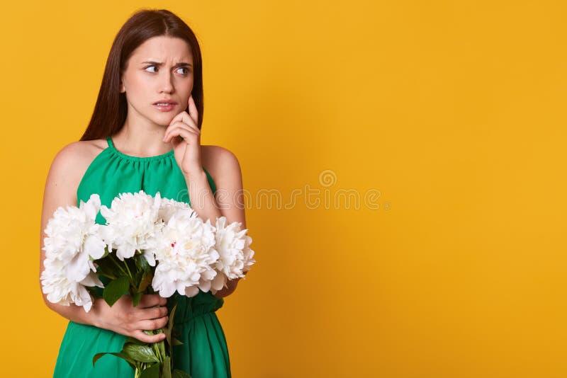 可爱的深色的妇女半身画象拿着白色牡丹的花束在黄色背景的绿色sundress的, 免版税库存图片