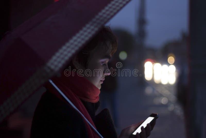 可爱的深色的妇女在伞在晚上和在智能手机的看照片下有触摸屏幕技术的 复制 免版税库存图片