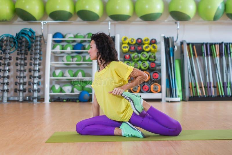 可爱的深色的少妇坐席子准备活动在训练前舒展她的在微笑的健身房的四头肌和 库存照片