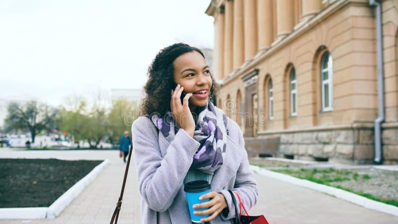 可爱的混合的族种女孩谈的智能手机和饮用的咖啡步行在城市街道有袋子的 走的妇女年轻人 库存图片