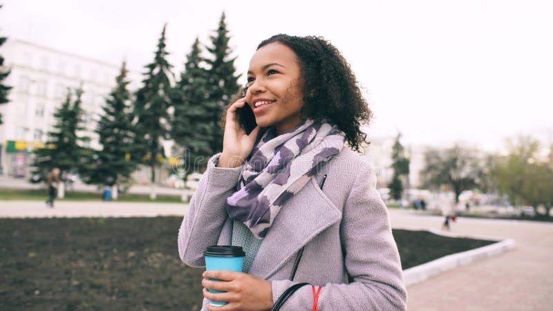 可爱的混合的族种女孩谈的智能手机和饮用的咖啡步行在城市街道有袋子的 走的妇女年轻人 免版税库存图片