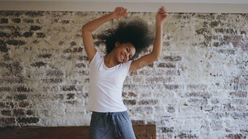 可爱的混合的族种年轻快乐的妇女获得在家跳舞在床附近的乐趣 免版税库存照片