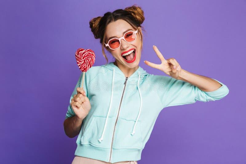 可爱的滑稽的女孩的图象用吃两个的小圆面包举行和 库存图片