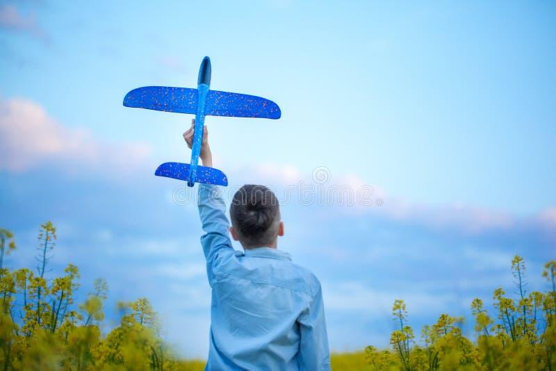 可爱的男孩在夏日在他的手上拿着玩具飞机在日落 r 库存照片