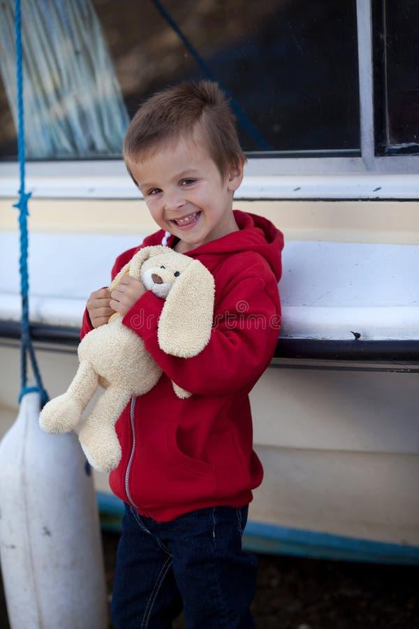 可爱的男孩,拿着他的玩具熊,微笑 库存照片