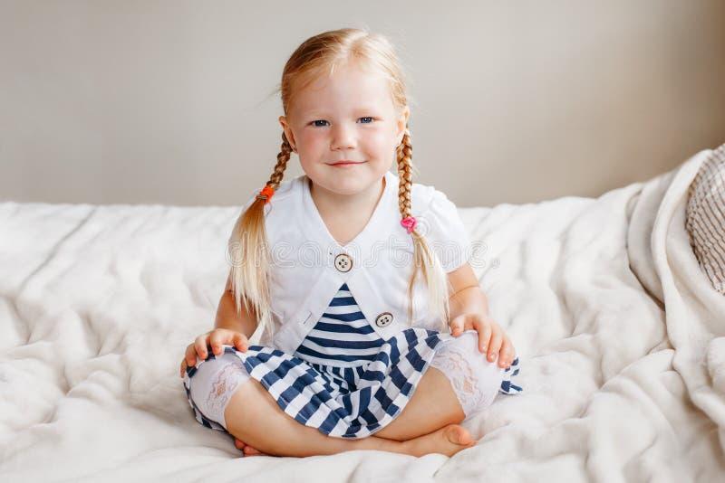 可爱的白白种人微笑的学龄前女孩坐看在照相机的床 免版税库存图片