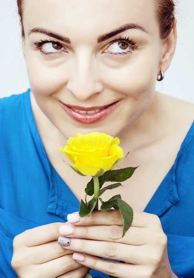年轻可爱的白种人妇女嗅黄色玫瑰 库存照片