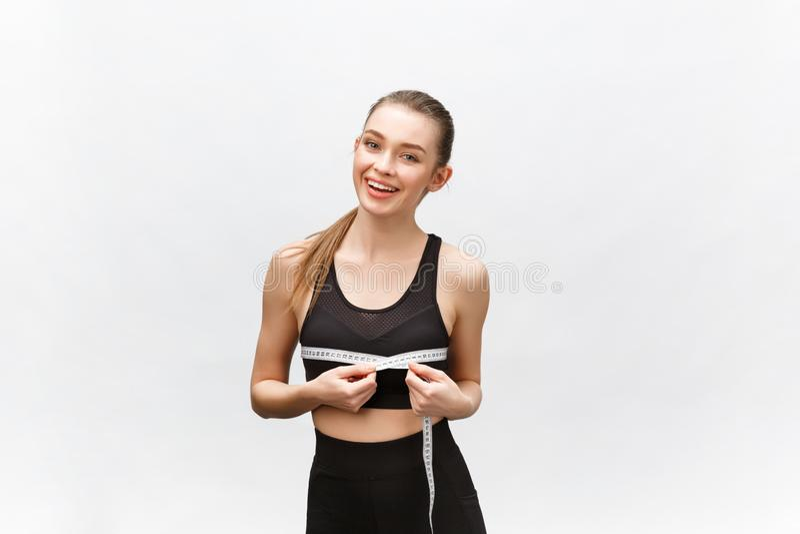 可爱的白种人微笑的妇女画象有在白色背景隔绝的测量的磁带的 免版税库存照片