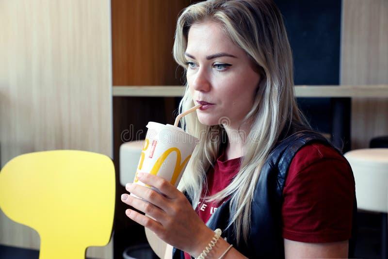 可爱的白肤金发的与秸杆的年轻女人饮用的苏打 免版税库存图片