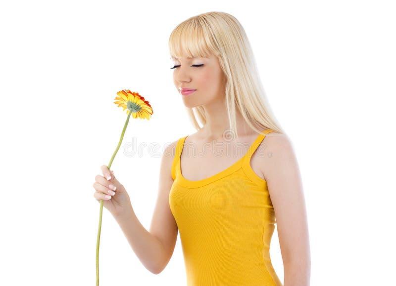 可爱的白肤金发的妇女嗅到的雏菊 图库摄影