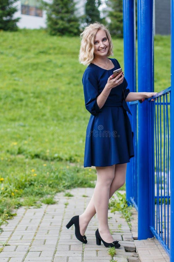 年轻可爱的白肤金发的妇女在夏天公园 库存照片
