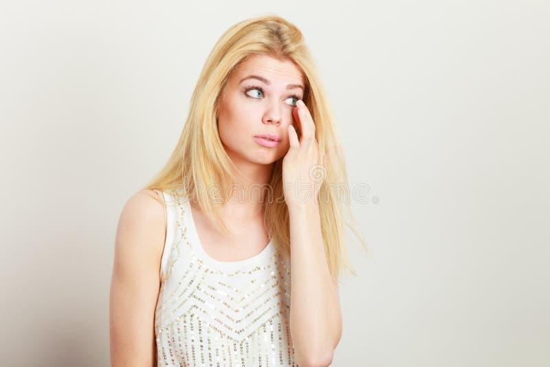 可爱的白肤金发的妇女有某事在眼睛 免版税库存照片