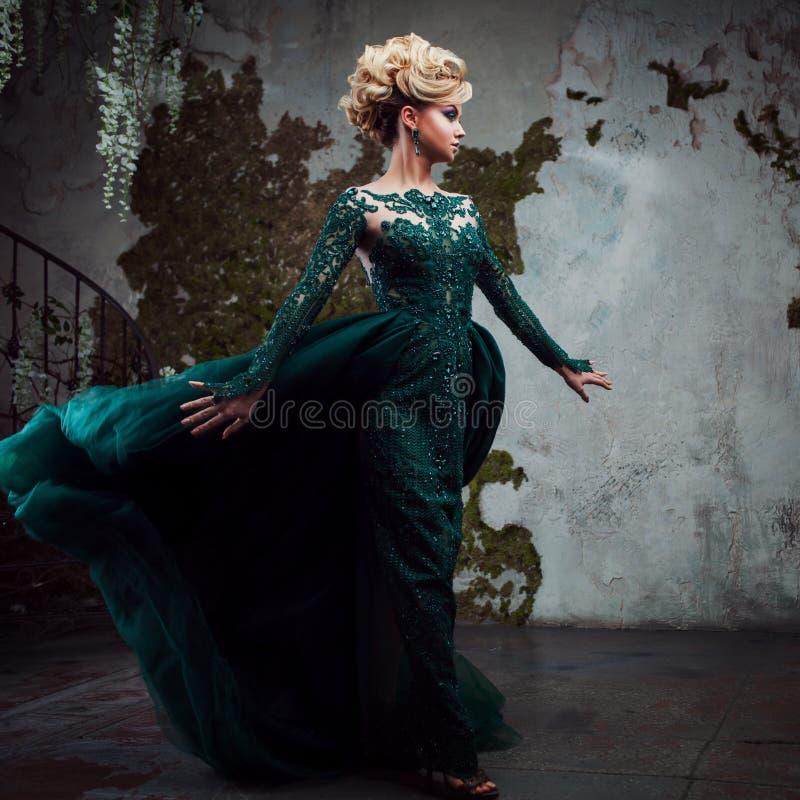 年轻可爱的白肤金发的妇女画象一件美丽的绿色礼服的 织地不很细背景,内部 豪华发型 库存图片