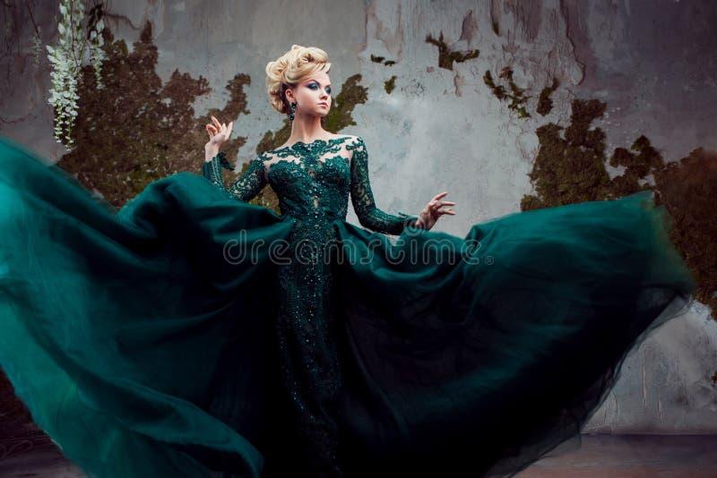 年轻可爱的白肤金发的妇女画象一件美丽的绿色礼服的 织地不很细背景,内部 豪华发型 免版税库存照片