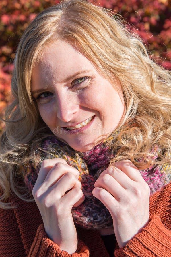 可爱的白肤金发的妇女画象反对常春藤的在秋天 免版税库存照片