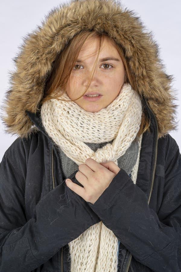 可爱的白肤金发的少年模型在演播室环境里的穿一件冬天外套 免版税库存照片