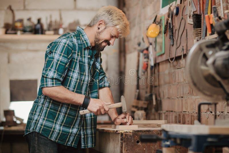 可爱的白肤金发的年轻由行业钉牢有锤子的木匠建造者的行家有胡子的人木委员会在木 免版税库存图片