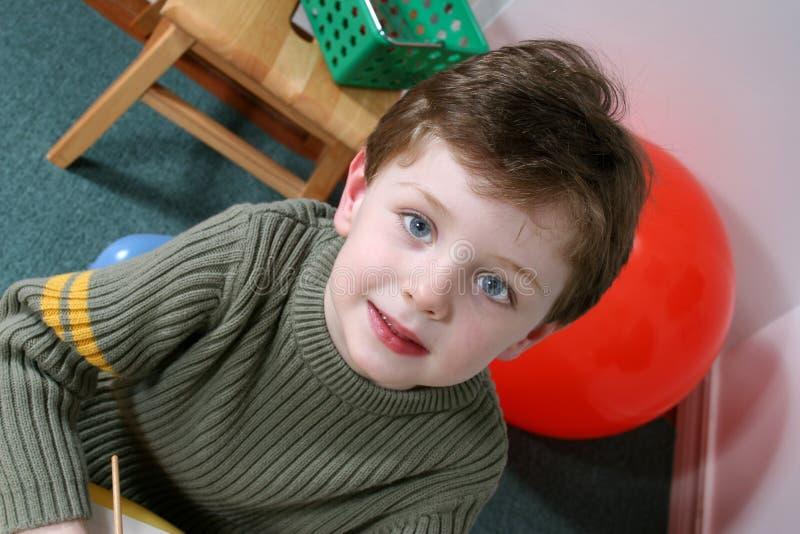 可爱的白肤金发的穿蓝衣的男孩注视四根头发老年 免版税库存图片