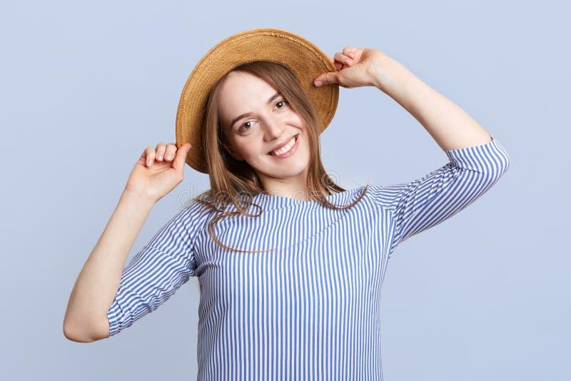 可爱的相当少妇特写穿草帽,并且镶边女衬衫,在好心情,高兴以后的假期,去的t 库存图片
