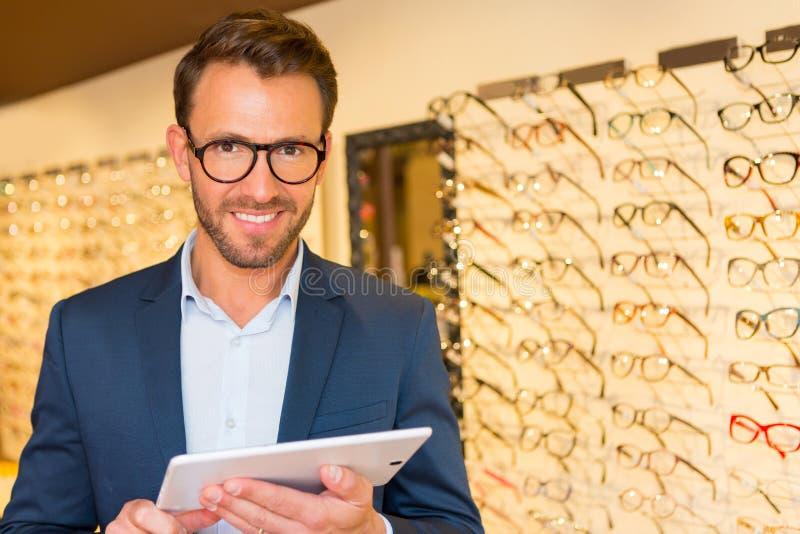 可爱的眼镜师与在他的玻璃的片剂一起使用购物 库存照片