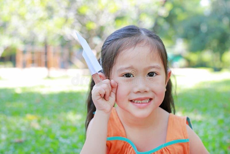 可爱的矮小的亚洲儿童女孩折叠每片断对火箭的白皮书和显示在她的食指在室外绿色的庭院里 免版税库存图片