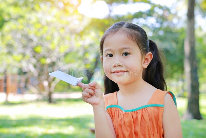 可爱的矮小的亚洲儿童女孩折叠每片断对火箭的白皮书和显示在她的食指在室外绿色的庭院里 库存照片