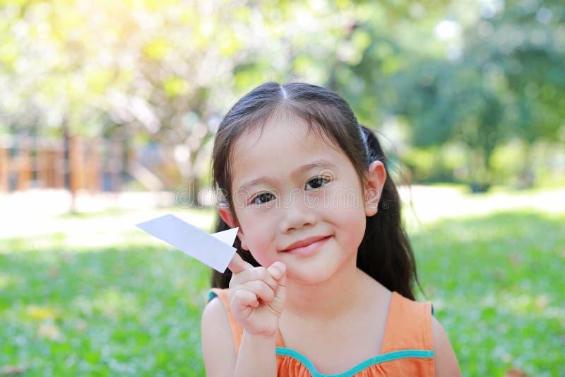可爱的矮小的亚洲儿童女孩折叠每片断对火箭的白皮书和显示在她的食指在室外绿色的庭院里 免版税库存照片