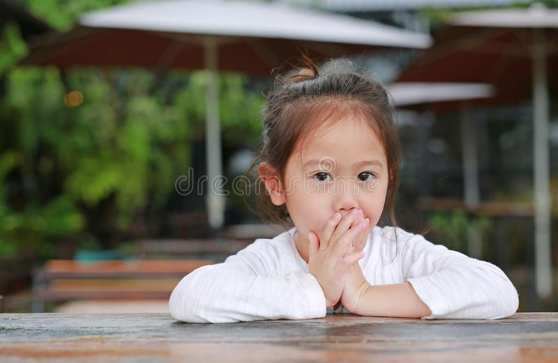 可爱的矮小的亚裔儿童女孩用手用看照相机盖她的说谎在木桌上的嘴 图库摄影