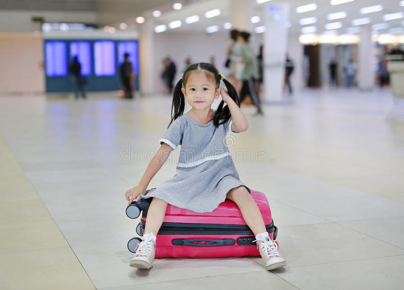 可爱的矮小的亚裔女孩在机场坐手提箱 图库摄影