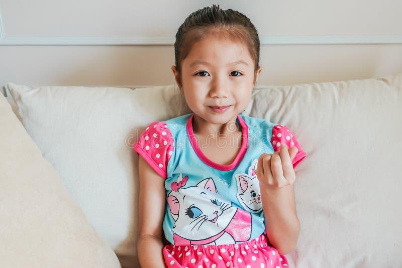 可爱的矮小的亚裔由拇指和食指的儿童女孩愉快的制造的微型心脏标志 免版税库存照片