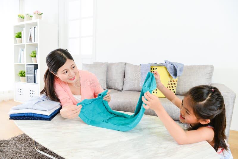 可爱的矮小的女儿折叠的家庭衣物 库存图片