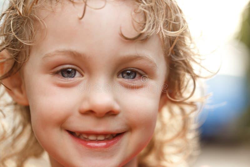可爱的矮小的白肤金发的女孩画象有卷发的 免版税图库摄影