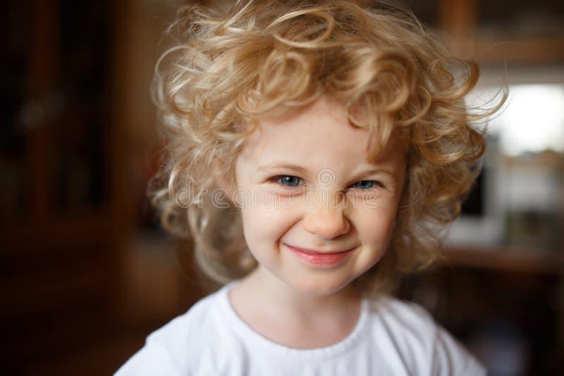 可爱的矮小的白肤金发的女孩画象有卷发的 库存图片