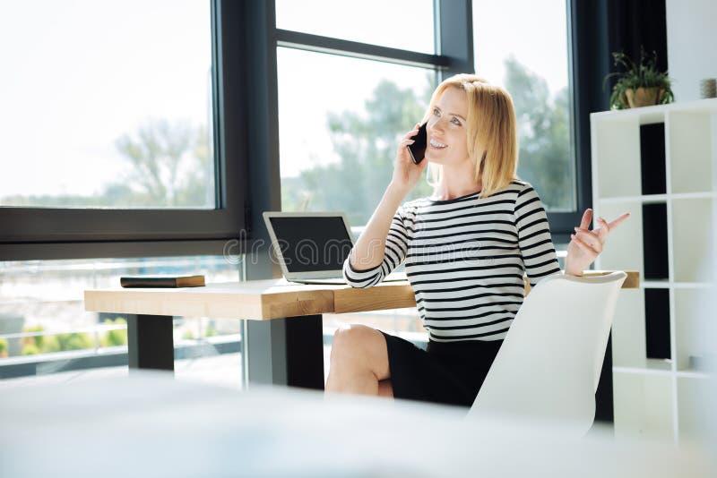 可爱的确信的女实业家谈话在电话 免版税库存照片