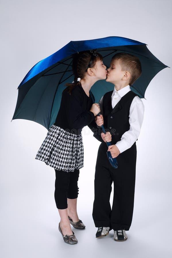 可爱的站立在伞下的男孩和女孩 免版税库存图片
