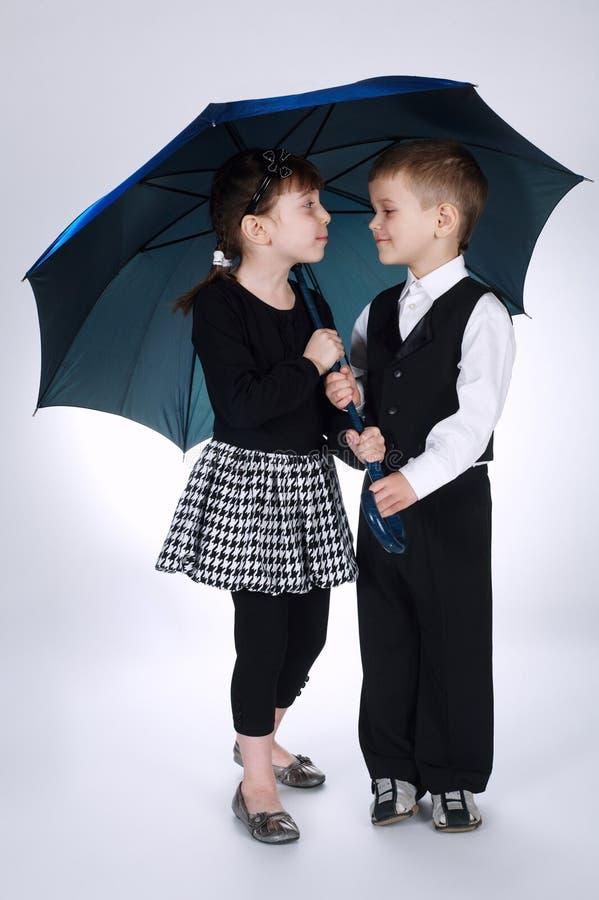 可爱的站立在伞下的男孩和女孩 图库摄影