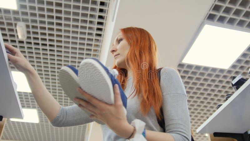 可爱的红发妇女选择在鞋店-购物概念的运动鞋 免版税图库摄影