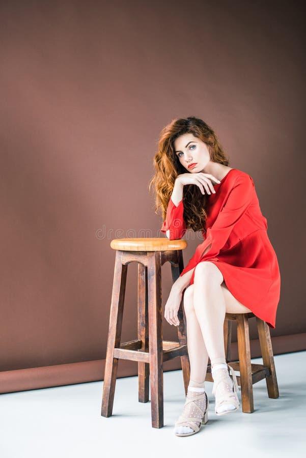 可爱的红头发人妇女坐椅子 免版税库存图片