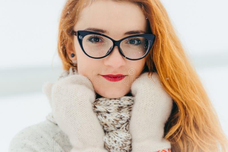 可爱的红色顶头妇女佩带的玻璃的深刻的视域 定期消费在降雪期间的乡下 免版税库存照片