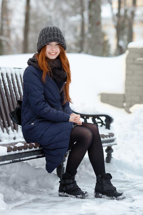 年轻可爱的红头发人妇女美丽的冬天画象在获得逗人喜爱的被编织的帽子的冬天乐趣坐长凳多雪的公园 库存照片