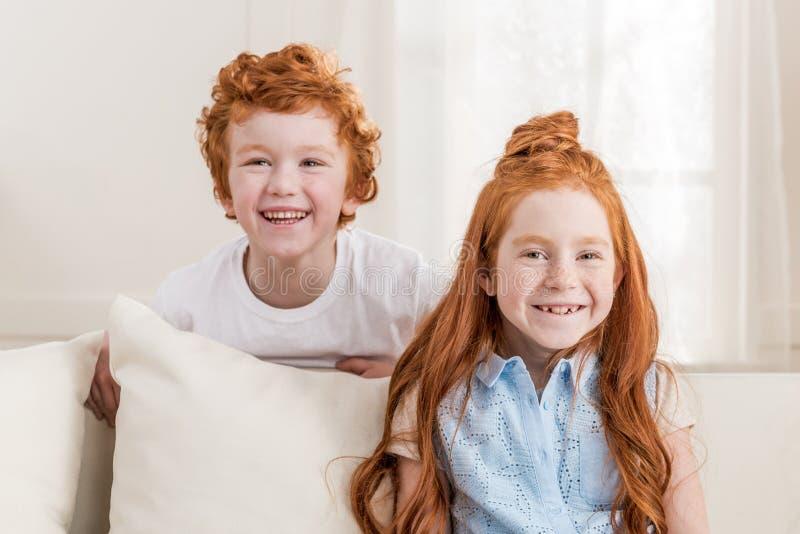可爱的红头发人姐妹和兄弟在家一起坐沙发 库存照片