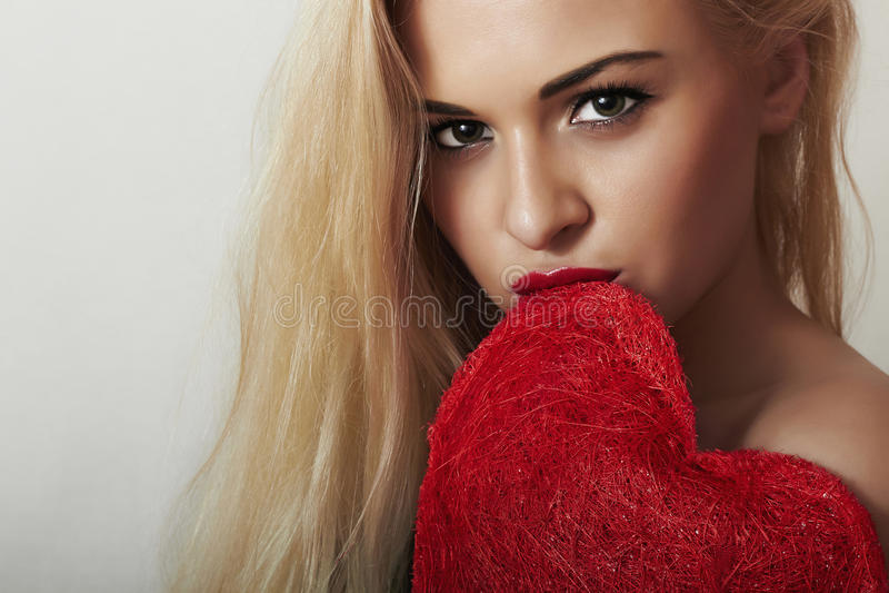 可爱的美丽的白肤金发的妇女咬住红色心脏。秀丽女孩。举行爱标志。情人节 免版税库存照片