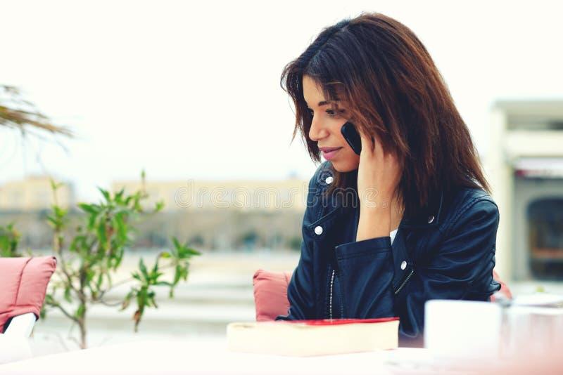 可爱的美国黑人的妇女谈话在巧妙的电话,当坐在咖啡店大阳台时 图库摄影