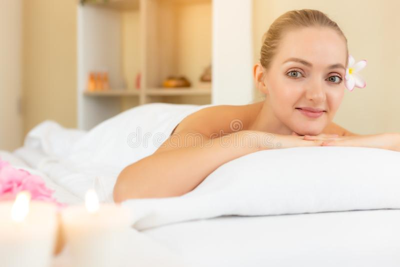 可爱的美女在床上放下在温泉沙龙 美好的年轻女人看看照相机和得到温泉满意的服务  图库摄影