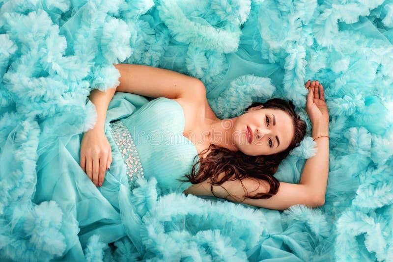 可爱的肉欲的嫩年轻女人在蓝色豪华的礼服云彩说谎  免版税库存图片